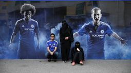 Suporter Chelsea berfoto dengan latar poster pemain Chelsea di luat stadion Stamford Bridge. (AFP Photo/Adrian Dennis)