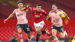 Penyerang Manchester United, Mason Greenwood, berusaha melewati pemain Sheffield United, Phil Jagielka dan Ethan Ampadu, pada laga Liga Inggris di Stadion Old Trafford,  Kamis (28/1/2021). MU takluk dengan  skor 1-2. (AP/Laurence Griffiths,Pool)