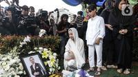 Bunga Citra Lestari atau BCL bersama anaknya Noah Sinclair memandangi foto Ashraf Sinclair saat pemakaman di San Diego Hills, Karawang, Jawa Barat, Selasa (18/2/2020). Ashraf Sinclair mengembuskan napas terakhir pukul 04.51 WIB pagi tadi. (Liputan6.com/Faizal Fanani)