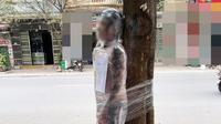 Seorang lelaki di Hanoi diikat dipohon dan dibungkus plastik karena tak bayar usai ditato (dok.phapluatvacuocsong.vn)