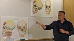 Liran Carmel menjelaskan model cetak 3D wajah gadis spesies manusia prasejarah Denisovan di Universitas Ibrani di Yerusalem (19/9/2019). Wajah gadis yang meninggal 40.000 tahun yang lalu di Siberia ini telah terungkap untuk pertama kalinya. (AFP Photo/Menahem Kahana)