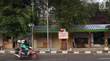 sepeda motor melintasi lapak kios di Sentra Lukisan Pasar Baru, Jakarta, Jumat (16/11). Sejumlah seniman lukis mengeluhkan kondisi lapak Sentra Lukisan Pasar Baru. (Liputan6.com/Immanuel Antonius)