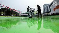 Pekerja membersihkan kolam di kompleks Parlemen, Senayan, Jakarta, Senin (31/7). Bersih - bersih ini dilakukan tiga bulan sekali untuk perawatan Gedung MPR/DPR/DPD. (Liputan6.com/Johan Tallo)