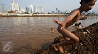 Anak-anak berenang di aliran air Kanal Banjir Barat, Jakarta, Kamis (26/11/2015). Dalamnya kali tidak menjadi penghalang bagi anak-anak tersebut untuk tetap bermain, meskipun berbahaya bagi keselamatan mereka. (Liputan6.com/Immanuel Antonius)