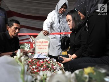 Warga membaca doa di depan makam Presiden ketiga RI BJ Habibie di TMP Kalibata, Jakarta, Kamis (12/9/2019). Tidak hanya dihadiri tokoh-tokoh penting, ratusan warga juga antusias datang ke TMP Kalibata untuk mengantarkan BJ Habibie ke tempat peristirahatan terakhirnya. (merdeka.com/Iqbal Nugroho)