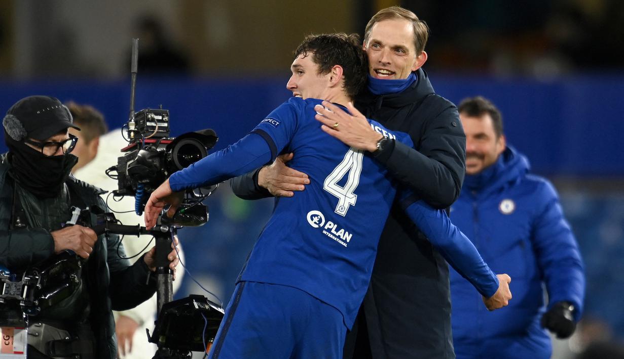 Pelatih Chelsea, Thomas Tuchel tersenyum saat memeluk bek Andreas Christensen usai pertandingan melawan Real Madrid pada leg kedua semifinal Liga Champions di Stamford Bridge di London, Kamis (6/5/2021). Chelsea menang atas Madrid 2-0 dengan aggregat 3-1. (AFP/Glyn Kirk)
