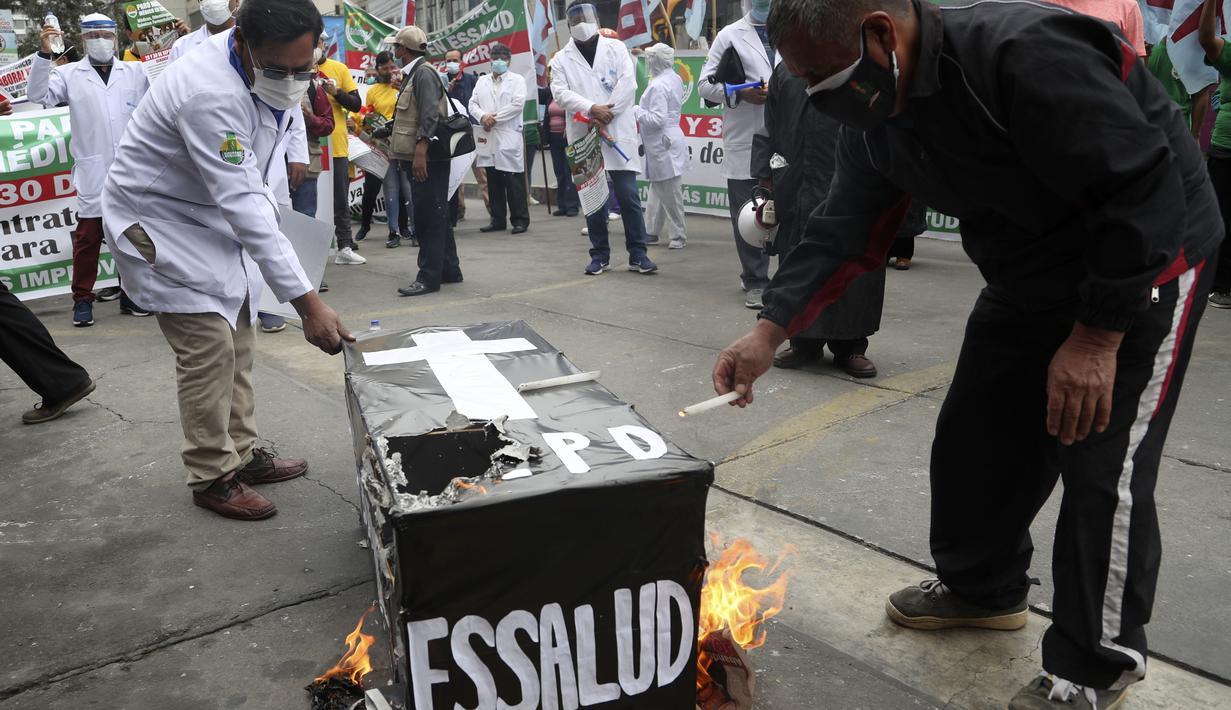 Petugas kesehatan membakar peti mati palsu saat mereka memprotes kurangnya alat pelindung bagi mereka yang merawat pasien COVID-19, di luar rumah sakit umum di Lima, Peru (29/9/2020). (AP Photo/Martin Mejia)