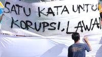 Warga menandatangani spanduk dukungan anti korupsi yang dibentangkan saat Hari Bebas Kendaraan di kawasan Bundaran HI, Jakarta, Minggu (10/12). Aksi dilakukan untuk memperingati Hari Anti-Korupsi Sedunia, 9 Desember. (Liputan6.com/Helmi Fithriansyah)
