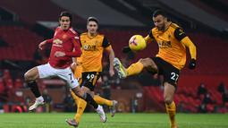Gelandang Wolverhampton Wanderers, Romain Saiss (kanan) menguasai bola di depan striker Manchester United, Edinson Cavani dalam laga lanjutan Liga Inggris 2020/21 pekan ke-16 di Old Trafford, Selasa (29/12/2020). Wolverhampton kalah 0-1 dari Manchester United. (AFP/Laurence Griffiths/Pool)
