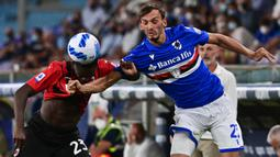 Pemain AC Milan Fikayo Tomori (kiri) berebut bola dengan pemain Sampdoria Manolo Gabbiadini pada pertandingan Serie A di Stadion Luigi Ferraris, Genova, Italia, 23 Agustus 2021. AC Milan menang 1-0. (MIGUEL MEDINA/AFP)