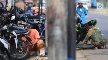 Sejumlah mekanik memperbaiki motor di salah satu bengkel di Otista, Jakarta, Minggu (10/6). Calon pemudik motor mulai memenuhi bengkel guna menyervis atau mengganti suku cadang kendaraan sebelum digunakan untuk mudik Lebaran. (Liputan6.com/Angga Yuniar)