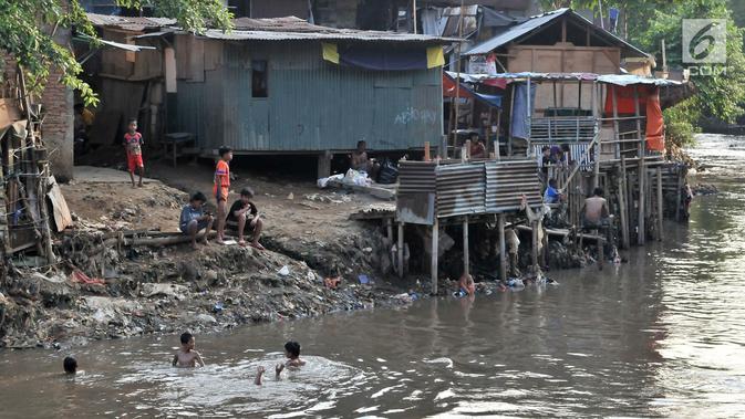 Anak-anak berenang di bawah jamban yang berada di bantaran Kali Ciliwung, Jakarta, Senin (19/11). Tak adanya akses sanitasi yang layak menyebabkan anak-anak menderita stunting. (Merdeka.com/Iqbal Nugroho)