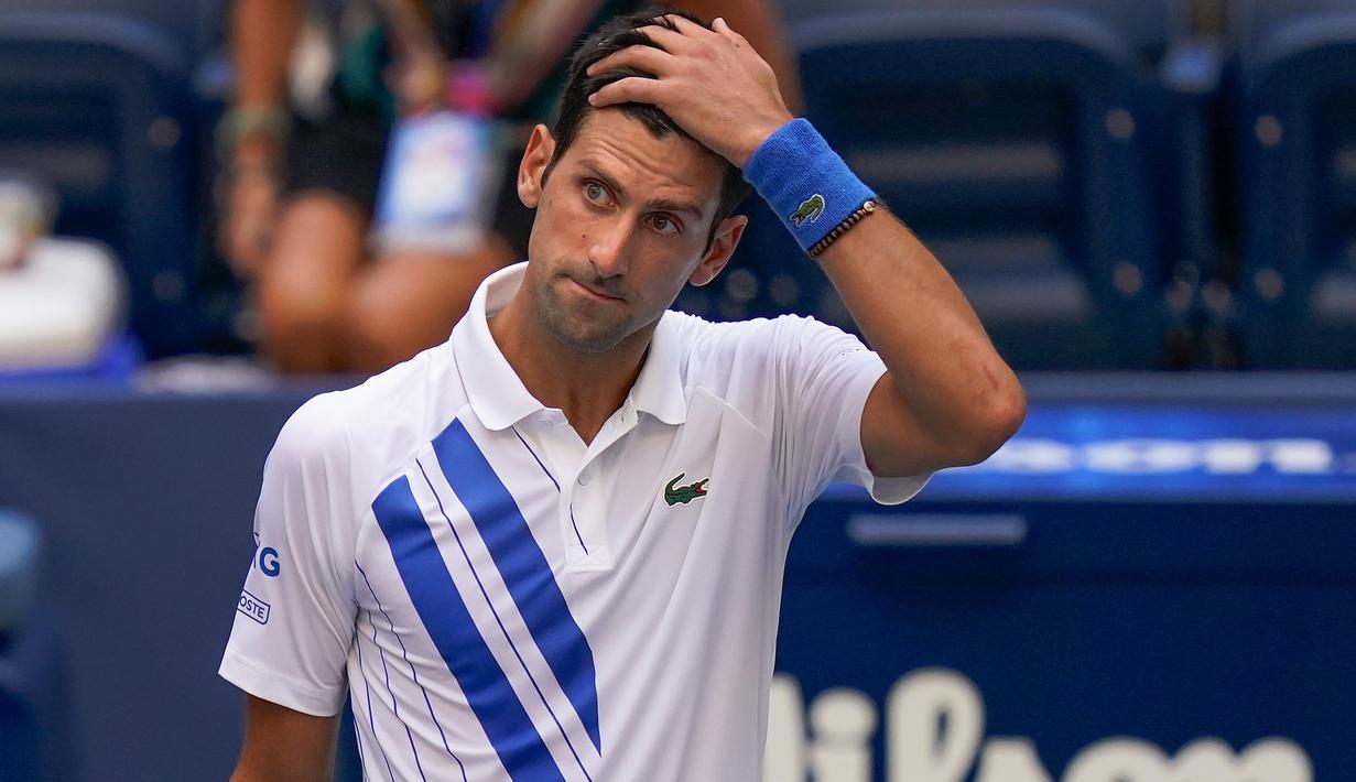 Reaksi petenis Serbia, Novak Djokovic setelah tidak sengaja memukulkan bola ke hakim garis saat kehilangan poin dari Pablo Carreno Busta (Spanyol) pada putaran keempat US Open 2020, di Flushing Meadows, Minggu (6/9/2020). Djokovic pun didiskualifikasi dari AS Terbuka 2020. (AP Photo/Seth Wenig)