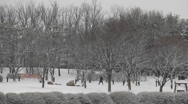 Pengunjung berjalan di salju dekat spanduk instruksi jarak sosial sebagai tindakan pencegahan virus corona di sebuah taman di Goyang, Korea Selatan, Kamis (28/1/2021). Hujan salju diperkirakan akan turun di sebagian besar negara itu pada hari Kamis dengan angin kencang kelas topan. (AP/Lee Jin-man)