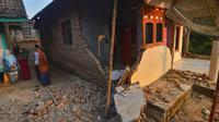 Warga berbincang dekat rumah yang rusak usai gempa melanda Pandeglang, Banten, Sabtu (3/8/2019). Sekitar 500 warga Kecamatan Sumur, Ujung Kulon, Kabupaten Pandeglang, masih mengungsi di Hunain Sementara (Huntara) akibat gempa Banten. (RONALD SIAGIAN/AFP)
