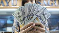 Petugas menunjukkan uang pecahan dolar Amerika di salah satu gerai penukaran mata uang di Jakarta, Jumat (18/5). Pagi ini, nilai tukar rupiah melemah hingga sempat menyentuh ke Rp 14.130 per dolar Amerika Serikat (AS). (Liputan6.com/Immanuel Antonius)