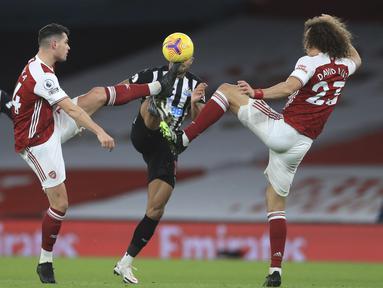 Penyerang Newcastle United, Callum Wilson berebut bola dengan dua pemain Arsenal Granit Xhaka dan David Luiz pada pertandingan Liga Inggris di Stadion Emirates di London, Selasa (19/1/2021). Arsenal menang telak atas Newcastle 3-0. (Adam Davy/Pool via AP)