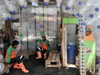 Petugas UPK Badan Air DLH DKI Jakarta bersantai dalam Pos Botol Plastik di Pasar Rebo, Jakarta, Selasa (12/3). Petugas memanfaatkan botol plastik bekas untuk membangun pos cantik. (merdeka.com/Iqbal Nugroho)