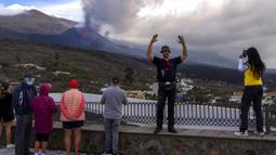 Wisatawan melihat dan mengambil foto gunung berapi yang meletus di Canary, Pulau La Palma, Spanyol, 26 Oktober 2021. Para pejabat mengatakan gunung berapi yang meletus selama lima minggu terakhir di Pulau La Palma lebih aktif dari sebelumnya. (AP Photo/Emilio Morenatti)