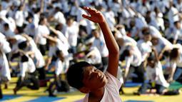 Seorang bocah melakukan gerakan yoga saat berlatih di Lapangan Independen di Kuala Lumpur, Malaysia (2/7). Acara yoga bersama ini bertemakan 'Yoga for Harmony & Peace'. (AP Photo / Daniel Chan)