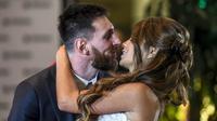 Bintang Barcelona, Lionel Messi, mencium bibir sang istri, Antonella Roccuzzo, dihadapan wartawan usai mengadakan resepsi pernikahan di Kompleks City Center, Santa Fe, Jumat (30/6/2017). (AFP/Eitan Abramovich)