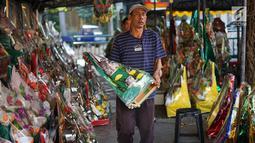 Pedagang membawa parsel yang dijual di kawasan Cikini, Jakarta, Selasa (28/5/2019). Penjualan parsel di kawasan ini menurun disebabkan turunnya permintaan, salah satunya akibat larangan menerima bingkisan bagi pejabat dan PNS di Indonesia oleh KPK. (Liputan6.com/Immanuel Antonius)