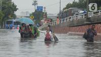 Warga RW 04 Kelurahan Jelambar melintasi banjir di Jakarta, Rabu (1/1/2020). Hujan yang turun saat pergantian tahun baru 2019-2020 menyebabkan sejumlah titik di kawasan Grogol terendam banjir. (merdeka.com/Imam Buhori)