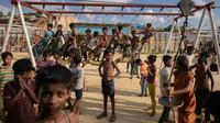 Anak-anak pengungsi Rohingya bermain ayunan di taman bermain di kamp pengungsi Thangkhali, dekat Cox's Bazar, Bangladesh, Kamis (9/8). (Ed JONES/AFP)