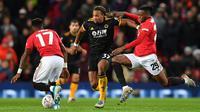 Pemain Wolverhampton Wanderers Adama Traore (tengah) mencoba melewati pemain Manchester United Fred (kiri) dan Aaron Wan-Bissaka pada putaran ketiga Piala FA di Old Trafford, Manchester, Inggris, Rabu (15/1/2020). Manchester United menang 1-0. (PAUL ELLIS/AFP)