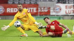 Striker Bayern Munchen, Robert Lewandowski, berebut bola dengan kiper Eintracht Frankfurt, Kevin Trapp, pada laga Piala Jerman di Allianz Arena, Rabu (10/6/2020). Bayern Munchen menang 2-1 atas Eintracht Frankfurt. (AP/Kai Pfaffenbach)