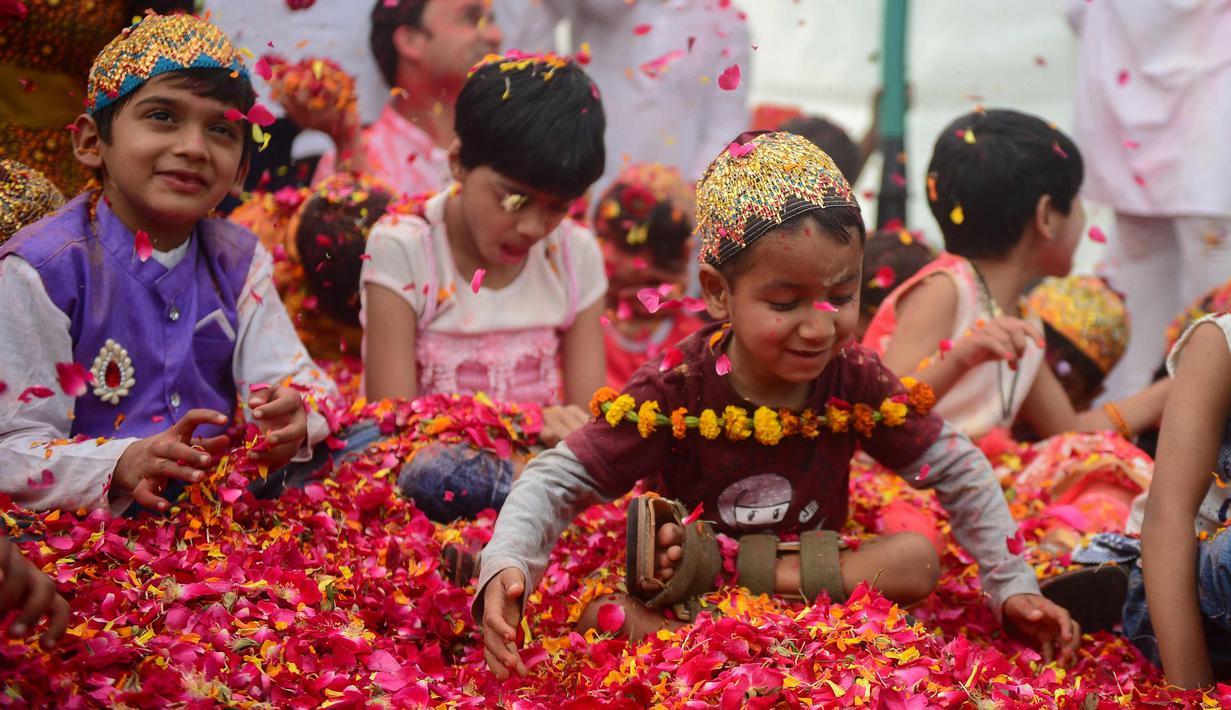 Anak-anak India bermain dengan kelopak bunga di sebuah acara untuk merayakan festival Hindu Holi untuk anak-anak cerebral palsy yang diselenggarakan oleh Yayasan Trishla di Allahabad (25/2). (AFP Photo/Sanjay Kanojia)