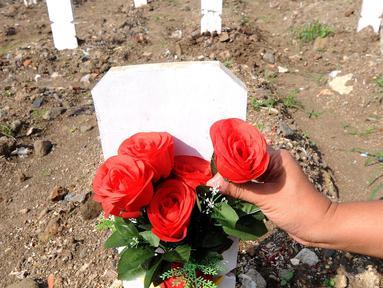 Warga meletakan bunga saat ziarah makam menyambut bulan Ramadan 1442 H di Tempat Pemakaman Umum (TPU) khusus covid-19 di Srengseng sawah 2, Jakarta Selatan, Jumat (09/04/2021). Tradisi ziarah makam dalam menyambut bulan Ramadhan setiap tahun dilakukan oleh umat Islam. (merdeka.com/Arie Basuki)