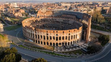 Foto udara pagi pada 30 Maret 2020, jalan-jalan sepi dan monumen Colosseum selama penerapan penutupan nasional atau lockdown di Roma. Roma menjelma bak kota mati pasca pemerintah Italia memberlakukan aturan lockdown di seantero wilayah untuk mencegah penyebaran virus corona. (Elio CASTORIA/AFP)