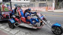 Wakil kandidat untuk Partai Sosial Liberal (PSL), Luiz Carlos de Paula yang dikenal sebagai Captain America menunggangi motor besar beroda tiga saat melakukan kampanye di Sao Paulo, Brasil, 26 September 2018. (AFP/NELSON ALMEIDA)