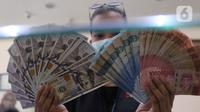 Petugas menunjukkan uang rupiah di penukaran uang, Jakarta, Senin (9/11/2020). ). Nilai tukar rupiah terhadap dolar AS bergerak menguat pada perdagangan di awal pekan ini Salah satu sentimen pendorong penguatan rupiah kali ini adalah kemenangan Joe Biden atas Donald Trump. (Liputan6.com/Angga Yuniar