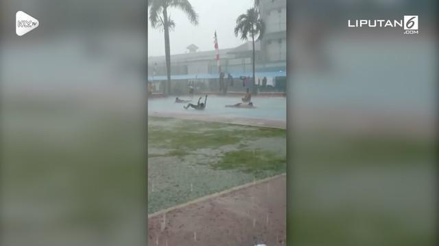 Seorang warga merekam momen unik saat para narapidana LP Cipinang bermain hujan-hujanan di lapangan basket.