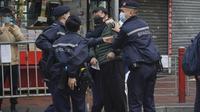 Seorang pria ditahan setelah menyerang petugas polisi saat ingin memasuki area tertutup di daerah Yordania di Hong Kong, Sabtu (23/1/2021). Penguncian diberlakuan setelah pihak berwenang memerangi wabah di salah satu distrik termiskin dan paling padat di kota itu. (AP Photo/Kin Cheung)