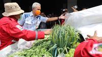 Gubernur Jawa Tengah Ganjar Pranowo saat mengecek bantuan sayuran yang akan dikirim ke korban bencana Jatim. (Foto: Liputan6.com/Felek Wahyu)