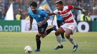Gelandang Persela, Jose Sardon (kiri), berduel dengan gelandang Madura United, Asep Berlian, di Stadion Surajaya, Lamongan, Minggu (31/3/2019). (Bola.com/Aditya Wany)