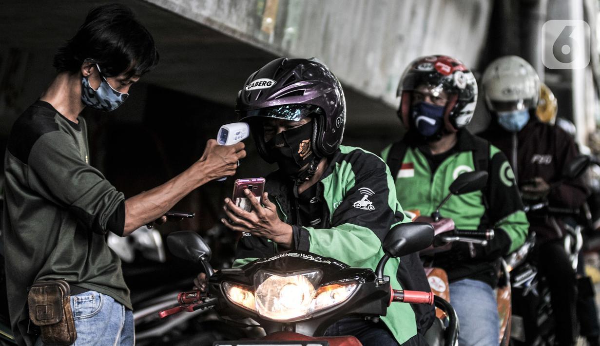 Petugas mengecek suhu tubuh pengojek daring saat pemeriksaan rutin di Posko Aman Covid-19, Jalan Ahmad Yani, Jakarta, Selasa (11/8/2020). Posko Aman Covid-19 rutin digelar untuk memeriksa kesehatan ojol guna mencegah penyebaran corona selama beroperasi di masa pandemi. (merdeka.com/Iqbal Nugroho)