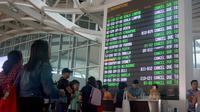 Sejumlah penumpang mencari informasi jadwal penerbangan di Bandara Ngurah Rai, Bali, Jumat (29/6). PT Angkasa Pura I menutup sementara operasional bandara selama 16 jam dikarenakan dampak abu vulkanik Gunung Agung. (AFP/GEDE ARDIASA)