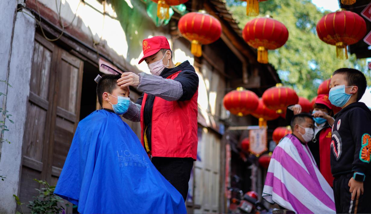 Seorang barber sukarelawan memotong rambut seorang anak laki-laki di sebuah permukiman di Kota Chongqing, China, pada 16 Februari 2020. Sejak merebaknya virus corona COVID-19, sebagian besar tempat potong rambut telah ditutup. (Xinhua/Liu Chan)