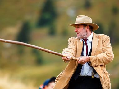 Seorang pria bermain permainan tradisional 'Gilihuesine' di resor pegunungan Bettmeralp, Swiss (16/9). Gilihuesine merupakan permainan campuran golf modern dan bisbol dan dimainkan sekali selama setahun di Bettmeralp. (Valentin Flauraud/Keystone via AP)