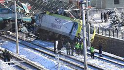 Tim penyelamat bekerja di lokasi kecelakaan kereta di Ankara, Turki, Kamis (13/12). Kejadian ini mengakibatkan empat orang tewas dan 47 lainnya terluka. (AP Photo/Burhan Ozbilici)
