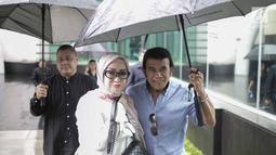 Rhoma Irama memayungi istrinya Ricca Rachim saat hadir dalam konferensi pers indosiar Ramadhan Penuh Berkah di Jakarta, Kamis (26/4). Pernikahan Rhoma Irama dan Ricca Rahim yang telah berusia 34 tahun ini jauh dari gosip. (Liputan6.com/Faizal Fanani)