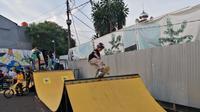 Seorang warga tengah asyik bermain skateboard di Tangerang. (Liputan6.com/Pramita Tristiawati)