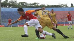 Pemain Bhayangkara Solo FC, Sani Rizki Fauzi (20), berebut bola dengan pemain Borneo FC Samarinda, M. Sihran H Amarullah, dalam pertandingan Babak Penyisihan Grup B Piala Menpora 2021 di Stadion Kanjuruhan, Malang. Senin (22/3/2021). (Bola.com/Arief Bagus)