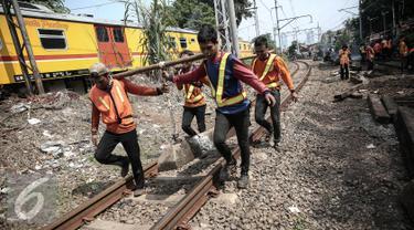 Petugas mengganti bantalan rel yang rusak pasca (KRL) Commuter Line Bogor-Tanah Abang yang anjlok di jalur Manggarai arah Sudirman, Jakarta, Rabu (18/5). KRL ka 1517 anjlok pada pukul 06.18 di km 5+4. (Liputan6.com/Faizal Fanani)