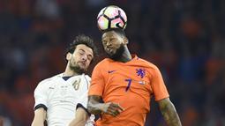 Gelandang Italia, Marco Parolo, duel udara dengan striker Belanda, Jeremain Lens. Belanda sebenarnya tampil lebih mendominasi dengan penguasaan bola hingga 56 persen sedangkan Italia hanya 44 persen. (AFP/John Thys)