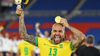 Dani Alves turut membantu Timnas Brasil meraih medali emas Olimpiade Tokyo 2020. Dengan pencapaian ini, Alves telah meraih 44 trofi juara. (AFP/Tiziana Fabi)